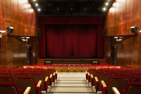 auditorium with red chairs and red curtain