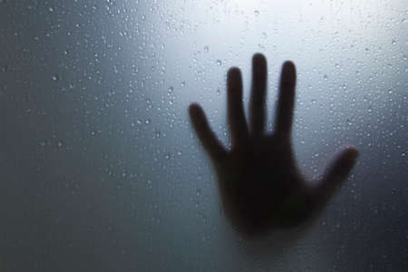 Fear concept, defocused hand silhouette outside window