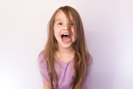 Photo pour Little girl with her hair, his mouth wide open, screaming, on a light background for any purpose - image libre de droit