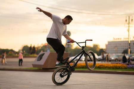 The guy performs a stunt on BMX, standing on the rear wheel. For any purpose.