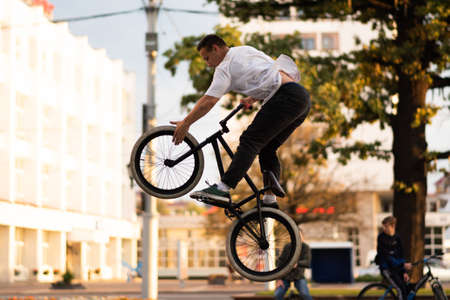 The guy performs a stunt on BMX, jumping up, and touches the front wheel.For any purpose.