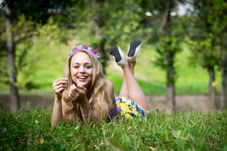 Photo for Beautiful blonde girl is lying in the grass and laughing. - Royalty Free Image