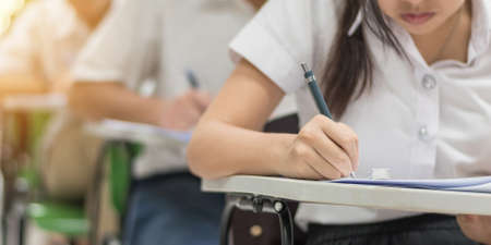 School exam, education concept with student taking examination or admission test writing answer in classroom with stress