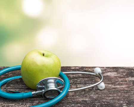 World health day concept with green natural nutrient apple with doctor\'s stethoscope