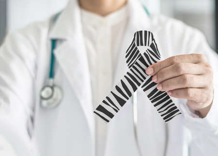 Photo pour Carcinoid Cancer Awareness ribbon zebra stripe black and white pattern symbolic bow color on doctor's hand support - image libre de droit