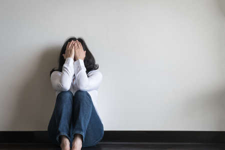 Photo pour Stressful woman sitting sadly with emotional depression and anxiety on the floor in home living room with white wall - image libre de droit