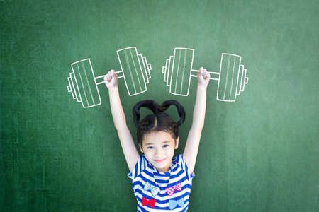 Photo pour Empowering woman and girl gender rights concept for international day of girl child, and sports for development and peace with healthy strong kid with dumbbell exercise doodle on school chalkboard - image libre de droit