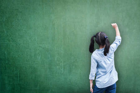 Photo pour Blank green classroom chalkboard background with student kid back view writing on board - image libre de droit