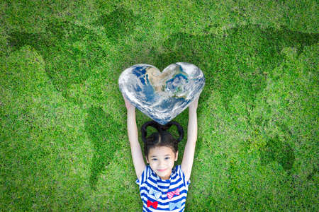 Foto de World heart day concept and well being health care campaign with smiling happy kid on eco friendly green lawn. - Imagen libre de derechos