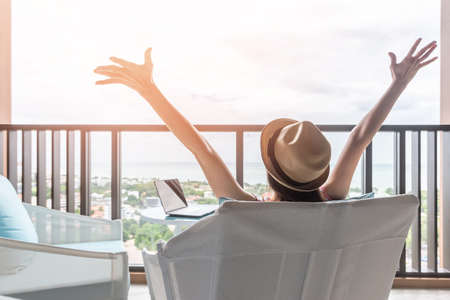 Foto de Life balance and summer holiday vacation concept with happy woman taking a break, celebrating successful work done, casually resting in luxury resort hotel workplace with computer pc laptop on desk - Imagen libre de derechos
