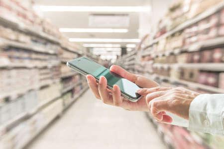 Photo pour Digital lifestyle business person or shopper using mobile smart phone for retail shopping in supermarket - image libre de droit
