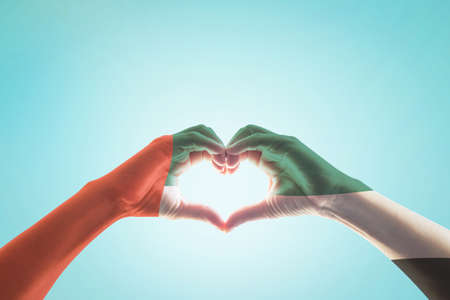 Photo pour UAE, United Arab Emirate national flag pattern on people's hands in heart shape on blue mint sky background - image libre de droit