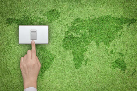 Photo pour Energy saving and ecological friendly concept with hand turning off switch on green grass lawn with world map - image libre de droit