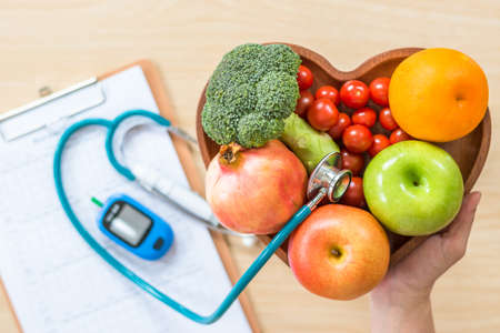 Foto de Diabetes monitor, Cholesterol diet and healthy food eating nutritional concept with clean fruits in nutritionist's heart dish and patient's blood sugar control record with diabetic measuring tool kit - Imagen libre de derechos