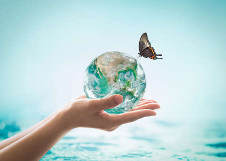 Photo pour World ocean day,, saving water campaign, sustainable ecological ecosystems concept with green earth on woman's hands on blue sea background - image libre de droit