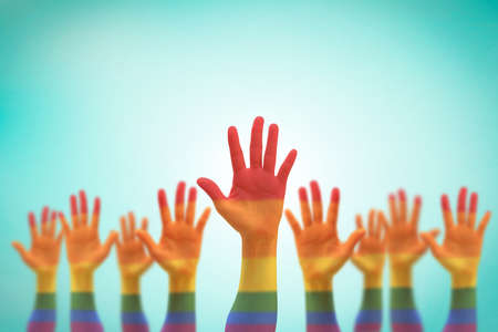 Foto de LGBT equal rights movement and gender equality concept with rainbow flag on people's hands up - Imagen libre de derechos
