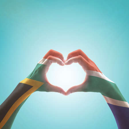 Foto de South Africa flag on woman hands in heart shape isolated on mint background for national unity, union, love and reconciliation concept - Imagen libre de derechos