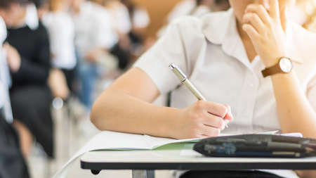 Foto de School student's taking exam, thinking hard, writing answer in classroom for educational university admission test  and world literacy day concept - Imagen libre de derechos