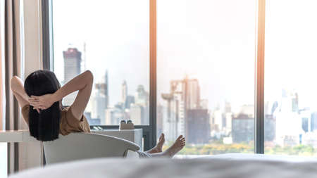 Photo pour Life quality concept with young woman relaxing and resting in comfort business hotel guest room or luxury home living room looking toward beautiful city view of cityscape - image libre de droit