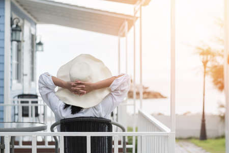 Photo pour Summer vacation lifestyle with young girl wearing sunscreen hat on sunny day relaxing taking it easy happily sitting on the porch at beach-house on beach front celebrating healthy living life quality - image libre de droit