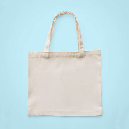 Foto de Tote bag mock up canvas white cotton fabric cloth for eco shoulder shopping sack mockup blank template isolated on pastel blue background (clipping path) - Imagen libre de derechos