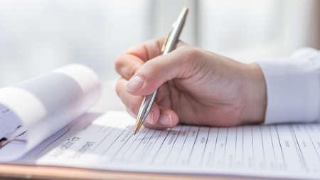 Foto de Applicant filling in company application form document applying for job, or registering claim for health insurance - Imagen libre de derechos