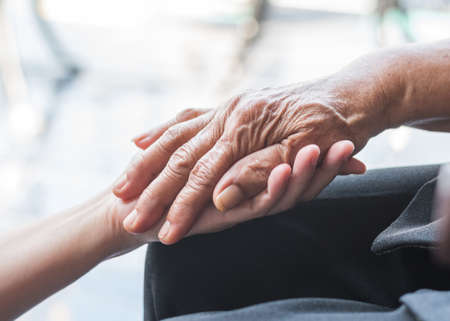 Photo pour Disability awareness day and aging society concept with Parkinson disease patient or elderly senior person in support of nursing family caregiver's hand - image libre de droit