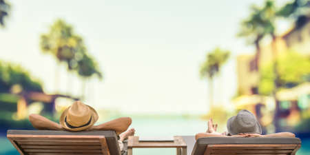 Photo pour Summer resort hotel stay relaxation with tourist traveller couple take it easy happily resting on beach chair on holiday travel vacation poolside peacefully at tropical beach swimming pool - image libre de droit