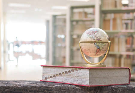 Foto de Globe model on textbook, or dictionary on  table in school or university library educational resource for knowledge - Imagen libre de derechos