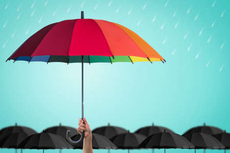 Foto de Life-health Insurance protection, business financial leadership concept with leader's hand holding rainbow umbrella distinctively unique - Imagen libre de derechos