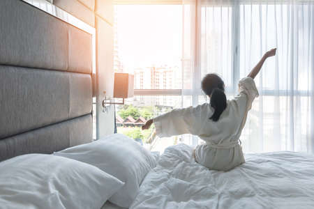 Photo pour Work-life quality balance concept with lazy lifestyle of Asian girl on bed relaxing in comfort city hotel bedroom, take it easy, resting from good sleep waking up on weekend morning having a good day - image libre de droit