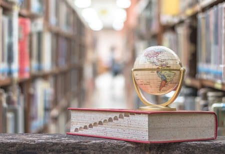 Foto de FEBRUARY 7, 2018 - BANGKOK, THAILAND: Globe model on textbook, or dictionary on  table in school or university library educational resource for knowledge - Imagen libre de derechos