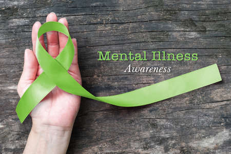 Photo pour Mental illness awareness with Lime Green ribbon color  on helping hand - image libre de droit