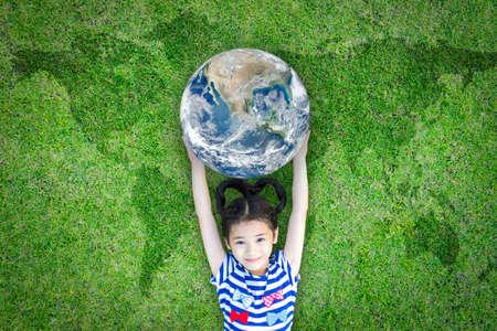 Foto de Earth day, ecological friendly and corporate social responsibility concept with kid raising world on green lawn - Imagen libre de derechos
