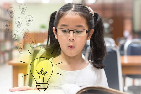 Photo pour Innovative creative idea for copyrights law concept with kid surprised reading book with lightbulb in library - image libre de droit