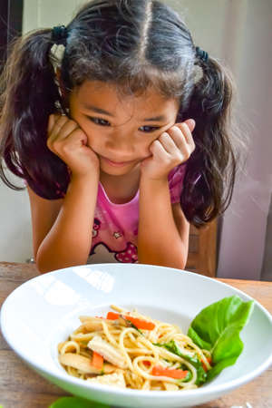 Photo pour Asian kid getting bored of food refusing meal with appetite loss, no hungry eating habit - image libre de droit