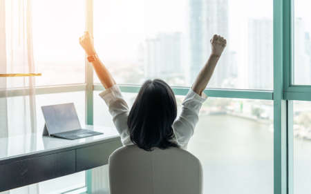 Photo pour Business achievement concept with happy businesswoman relaxing in office or hotel room, resting and raising fists with ambition looking forward to city building urban scene through glass window - image libre de droit