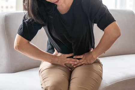 Foto de Abdominal pain in woman with stomachache illness from menstruation cramps, stomach cancer, irritable bowel syndrome, pelvic discomfort, Indigestion, Diarrhea or GERD (gastro-esophageal reflux disease) - Imagen libre de derechos