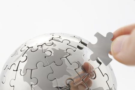 Foto de business concept with a hand building puzzle globe on white, space for messages  - Imagen libre de derechos