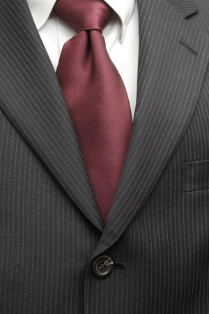 A pinstriped charcoal grey wool men's business suit with a silk tie and plain shirt.