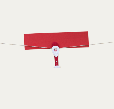 One christmas man with clothes peg on a cord, isolated on white