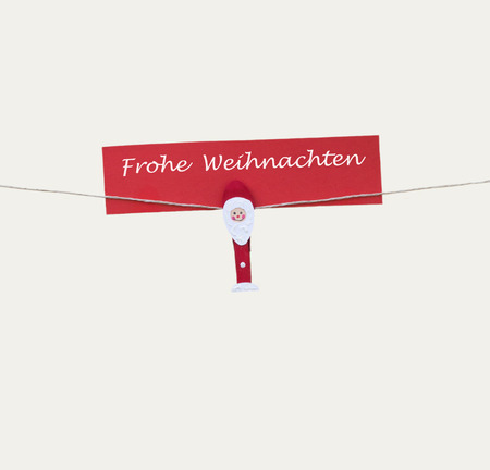 One christmas man with clothes peg on a cord and german text for merry christmas, isolated on white