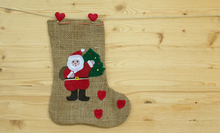 santa claus sock or stocking with clothes pegs on wood
