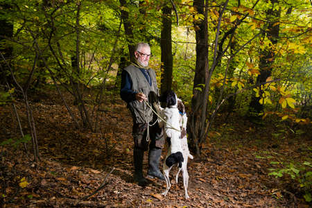 Photo pour Elderly man caresses his dogs while looking for truffles in the woods - image libre de droit