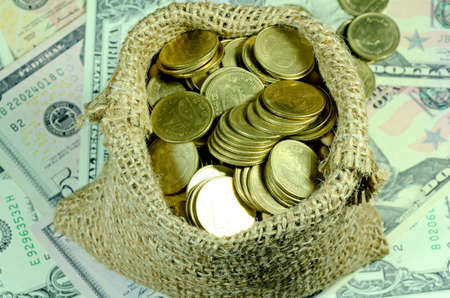 Gold Coins in Burlap Sack with Dollar Banknotes Background in Financial Concept