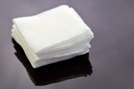 Photo pour Stack of sterile gauze pad on dark background. - image libre de droit