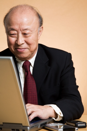 A shot of a senior asian businessman working on his laptop
