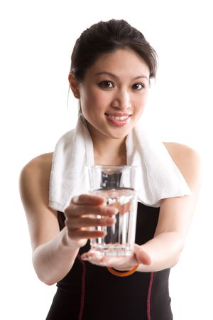An isolated shot of a healthy asian girl holding a glass of water