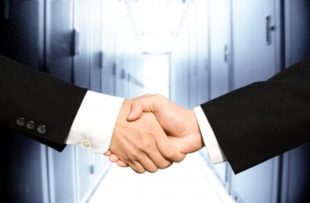 Photo pour Two businessmen shaking hands in a technology data center - image libre de droit