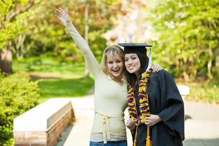 A happy beautiful graduation girl being congratulated by her friend
